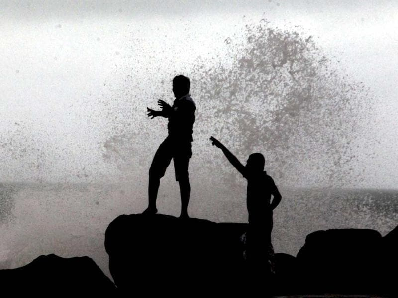 Boys play as waves strike the promenade at the fishing harbour in Chennai. PTI Photo