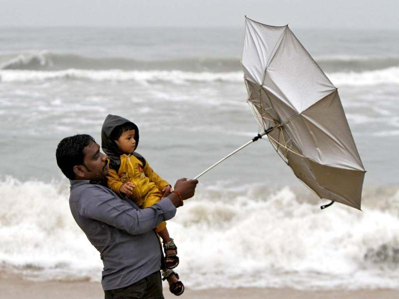 A man carrying his child tries to hold an umbrella at Marina beach in Chennai. Reuters Photo
