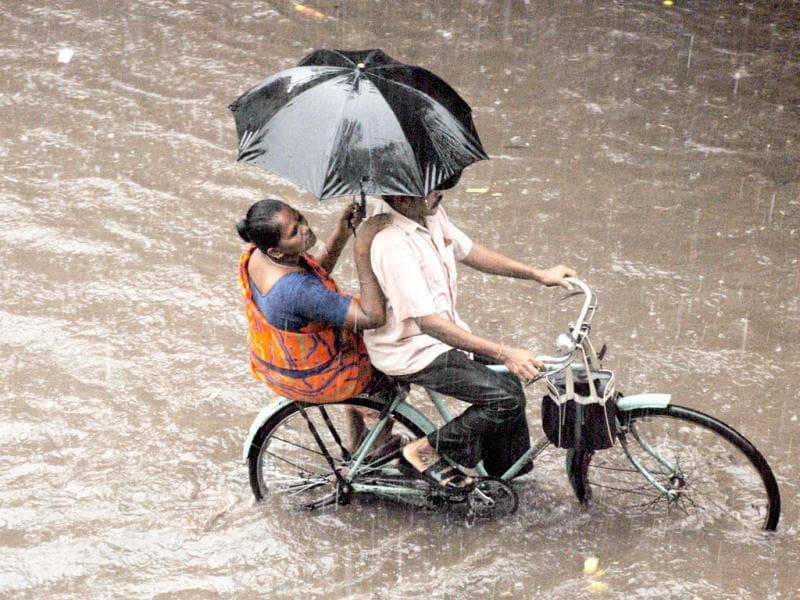 A man on a cycle rides through a water-logged road in Chennai. Agency Photo