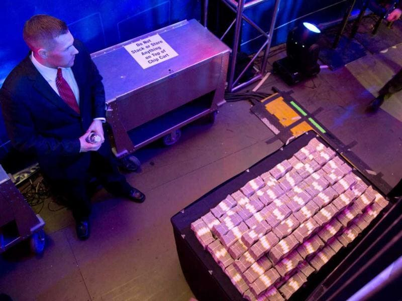 A security guard keeps watch over a stack of money backstage during the World Series of Poker Final Table event in Las Vegas. AP Photo/Julie Jacobson