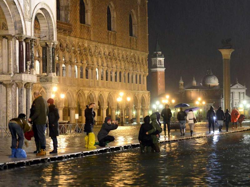 People walk on the flooded Saint Mark's square during an