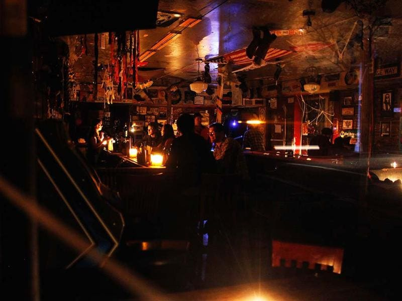 People sit in a bar lit by candlelight in the Lower East Village in the aftermath of Superstorm Sandy in New York. Reuters/Carlo Allegri