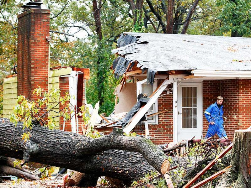 A firefighter leaves the destroyed home in Pasadena, Md where Donald Cannata Sr. was killed overnight when a tree fell on it during superstorm Sandy. AP Photo/Jose Luis Magana