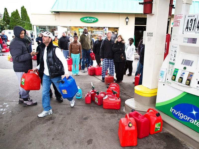 Customers form a queue to fill their gasoline canisters, in the Staten Island borough of New York. AP Photo/John Minchillo