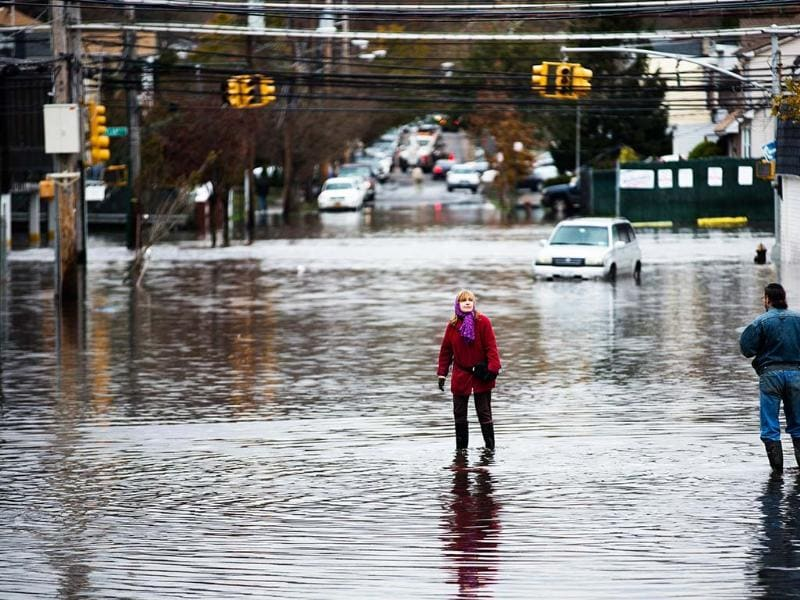 A woman stands in a street flooded by superstorm Sandy in the Staten Island borough of New York. AP Photo/John Minchillo
