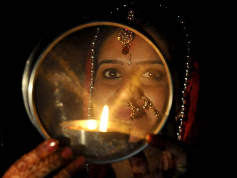 A Hindu woman poses while performing a ritual on the occasion of the festival of Karva Chauth in Siliguri . Karva Chauth is a fast undertaken by married Hindu women who offer prayers seeking the welfare, prosperity, well-being, and longevity of their husbands. FP PHOTO/Diptendu DUTTA