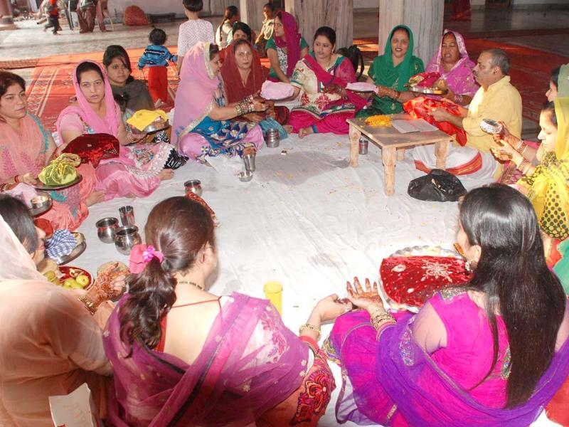 Women prepare to perfrom puja during Karva Chauth festival in Amritsar. Agencies