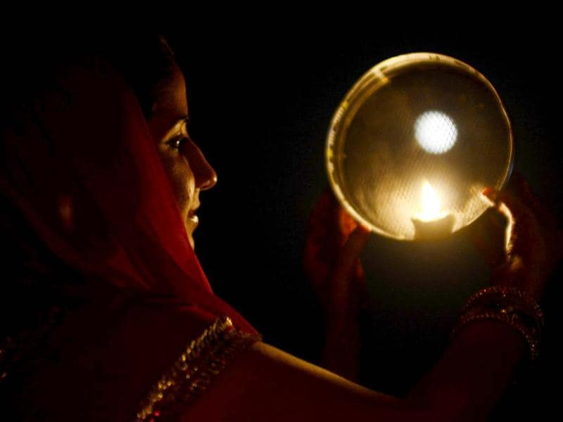 A Hindu woman poses while performing a ritual on the occasion of the festival of Karva Chauth in Amritsar . Married women observe Karvachauth by fasting and offering prayers seeking welfare, prosperity, and longevity of their husbands. AFP Photo/ Narinder Nanu