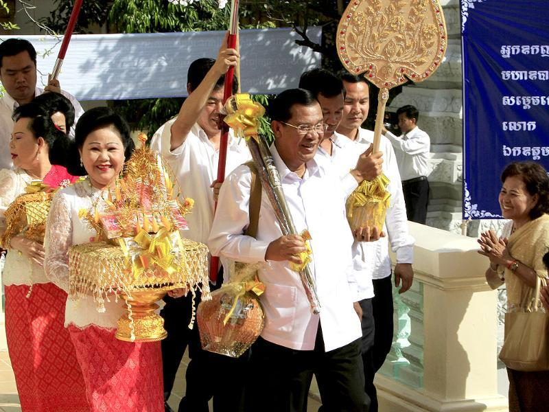 Cambodian Prime Minister Hun Sen walks together with his wife, Bun Rany, during a Buddhist ceremony called