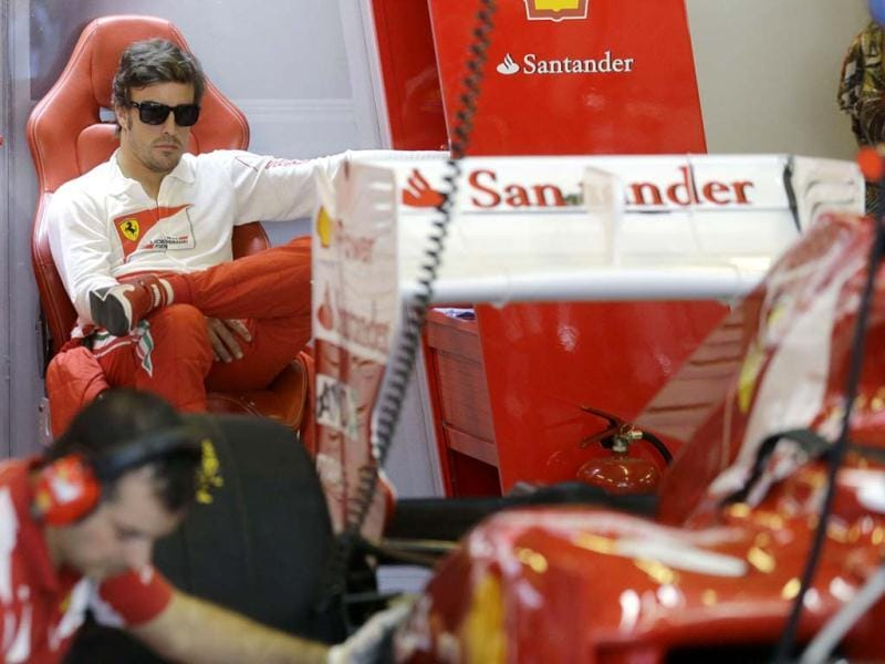 Ferrari driver Fernando Alonso of Spain watches as his car is serviced in the pits during the third free practice at the Yas Marina racetrack, in Abu Dhabi, United Arab Emirates. AP Photo