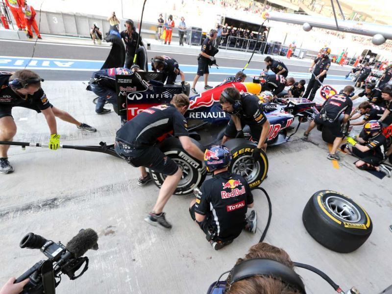 Mechanics change tires on the car of Red Bull Racing's German driver Sebastian Vettel in the pits during the third practice session at the Yas Marina circuit in Abu Dhabi ahead of the Abu Dhabi Formula One Grand Prix. AFP Photo