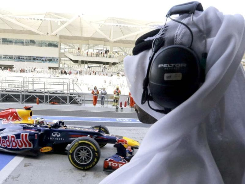 A journalist watches Red Bull driver Sebastian Vettel of Germany as he steers his car back to pits during the third free practice at the Yas Marina racetrack, in Abu Dhabi, United Arab Emirates. AP Photo