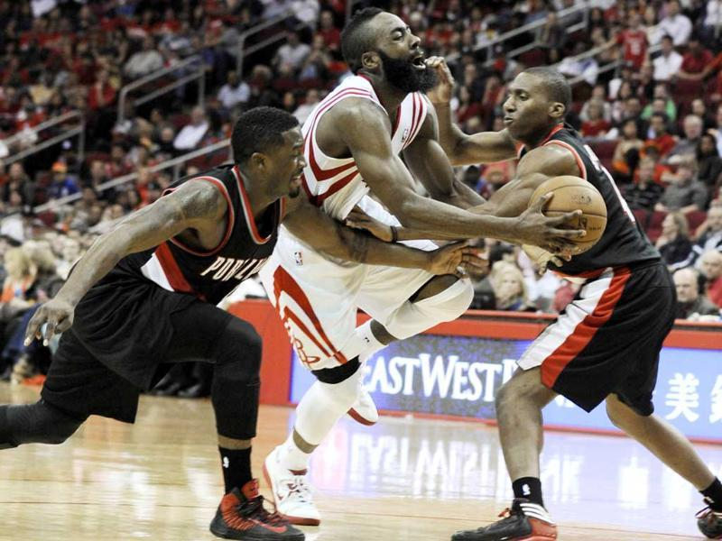 Houston Rockets shooting guard James Harden is fouled by Portland Trail Blazers' Nolan Smith as Wesley Matthews reaches in in the second half of an NBA basketball game in Houston. AP/Pat Sullivan