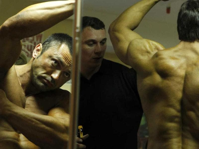 Participants prepare backstage during the international bodybuilding tournament