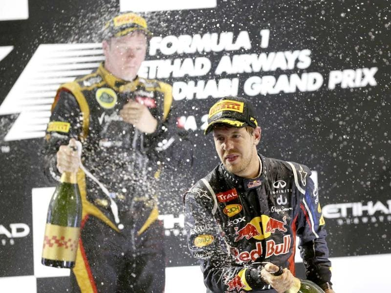 Third place Red Bull driver Sebastian Vettel of Germany sprays rose water as he celebrates on the podium during the Emirates Formula One Grand Prix, at the Yas Marina racetrack, in Abu Dhabi, United Arab Emirates. AP photo