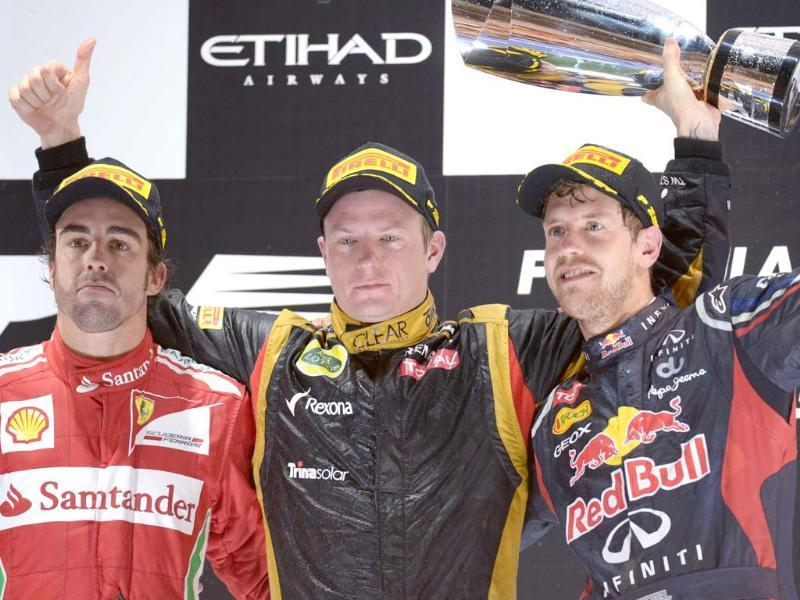 Ferrari's Spanish driver Fernando Alonso, Lotus F1 Team's Finnish driver Kimi Raikkonen and Red Bull Racing's German driver Sebastian Vettel celebrates on the podium at the Yas Marina circuit in Abu Dhabi after the Abu Dhabi Formula One Grand Prix. AFP