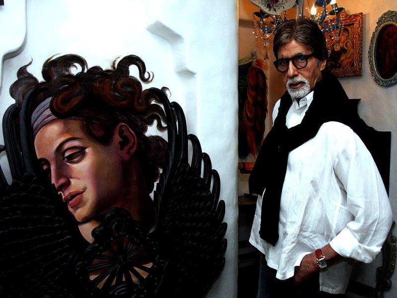 Amitabh Bachchan poses next to a piece on display at an art show in Mumbai.