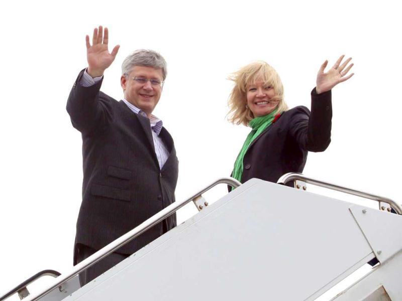 Canadian Prime Minister Stephen Harper and his wife Laureen wave while boarding their plane before departing for India to boost bilateral trade and economic ties, in Ottawa. Reuters
