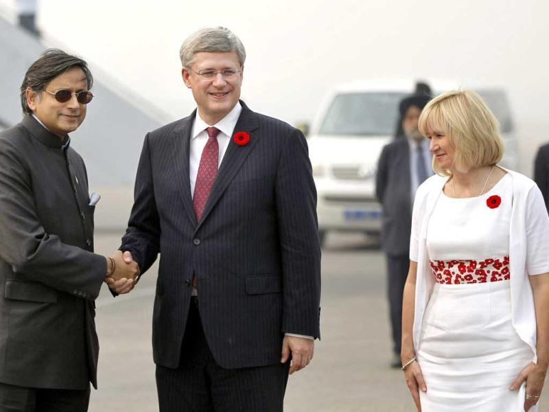 Canada's Prime Minister Stephen Harper, center, and his wife Laureen Ann, are greeted by Minister of State for Human Resource Development Shashi Tharoor upon their arrival at the Indira Gandhi International Airport in New Delhi. AP Photo/Mustafa Quraishi