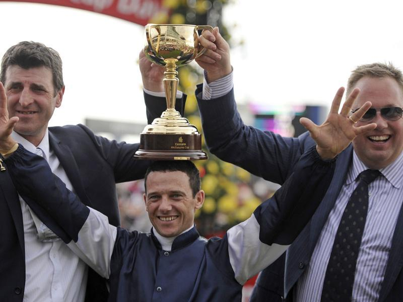 Jockey Brett Prebble, center, celebrates with the winning trophy held by his trainer Robert Hickmott, left, and owner of Green Moon Nick Williams, on his head after Green Moon won the Melbourne Cup at Flemmington Race Course in Melbourne, Australia. AP/Andrew Brownbill
