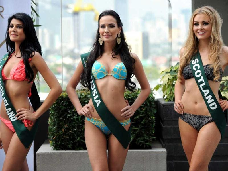 Contestants Aisha Valy of Reunion Island, Natalia Pereverzeva of Russia, and Sara Pender of Scotland pose for photographers during a press presentation of the Miss Earth beauty pageant at a hotel in Manila. (AFP Photo)