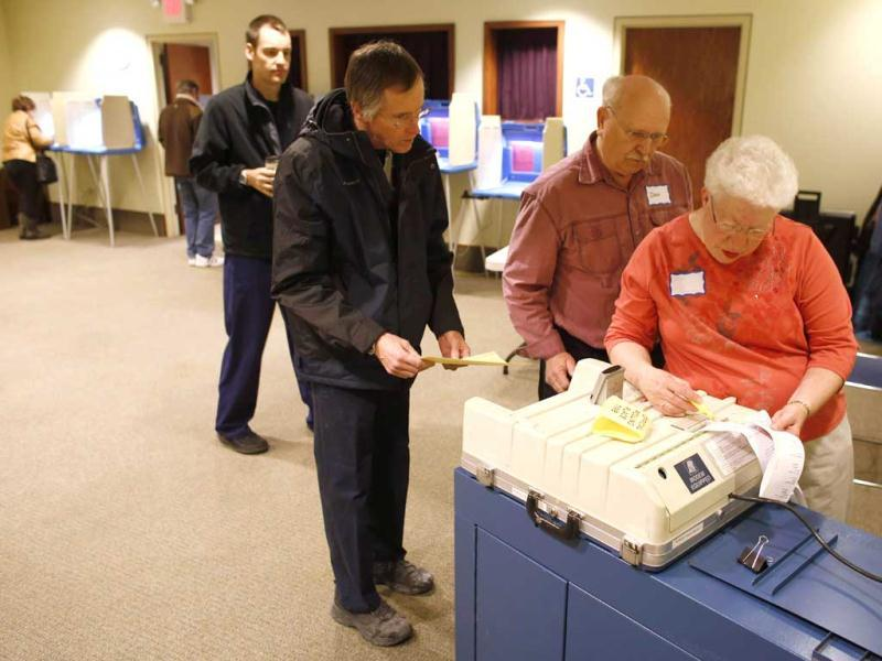Poll workers Don Allison (2nd-R) and Bertha Janis ¨ chief Inspector of the polling stations go over a ballot that was rejected by the machine while voters wait in line to cast their vote in the Presidential elections in Janesville Wisconsin. AFP photo