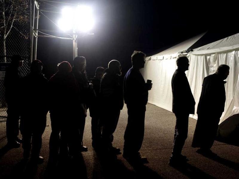 Under the lights of a generator, voters wait in line outside of a tent serving as a polling site in the Midland Beach section of Staten Island, New York, on Election Day. AP photo