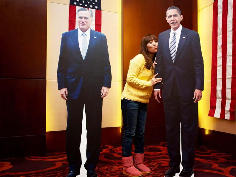 A visitor poses with cut-out replicas of US President Barack Obama and Governor Mitt Romney during a '2012 US Election Watch' event organized by the US embassy in Seoul. AFP photo