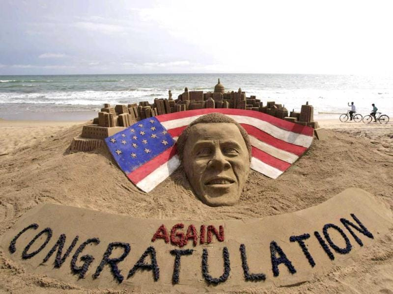 Cyclists ride on a beach passing by a sand sculpture congratulating US president Barack Obama for a second term in office in Puri, Orissa. AP Photo/Biswaranjan Rout