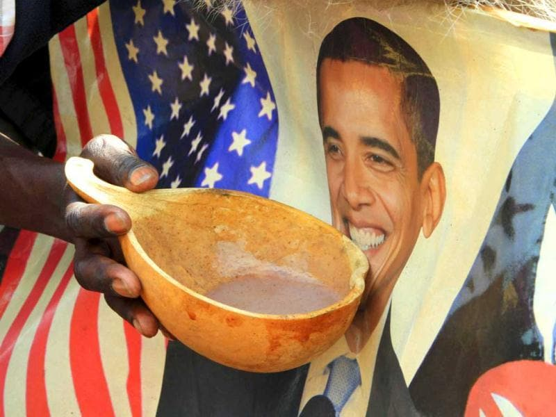 A person holds a bowl of local porridge against a poster of US President Barack Obama as they celebrate his re-election in the sprawling Kibera slums of Kenya's capital Nairobi. Reuters/Noor Khamis