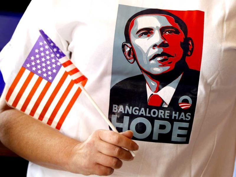A supporter of President Barack Obama holds a flag and sports a T-shirt which has a portrait of Obama and a phrase that reads 'Bangalore has hope' during a screening of US elections coverage organized at a restaurant over breakfast in Bangalore. AP Photo/Aijaz Rahi