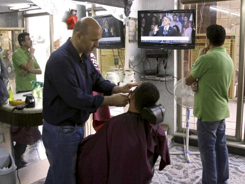 Palestinians at a barber shop watch a televised speech by US President Barack Obama after his vicotry, in the West Bank town of Jenin. AP Photo/Mohammed Ballas