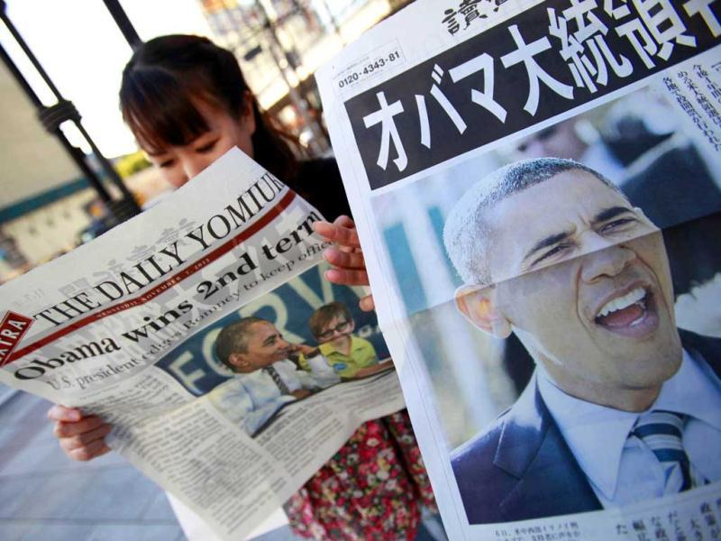 A woman reads an extra edition of a newspaper reporting US President Barack Obama's re-election in Tokyo. Reuters Photo/Yuriko Nakao