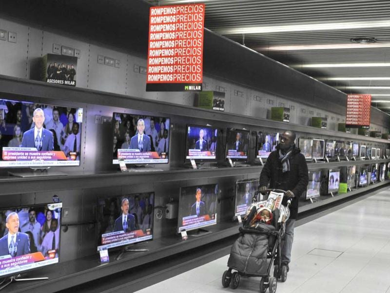 A man walks past TV screens portraying newly elected US President Barack Obama, in a store in Pamplona, northern Spain. AP Photo/Alvaro Barrientos
