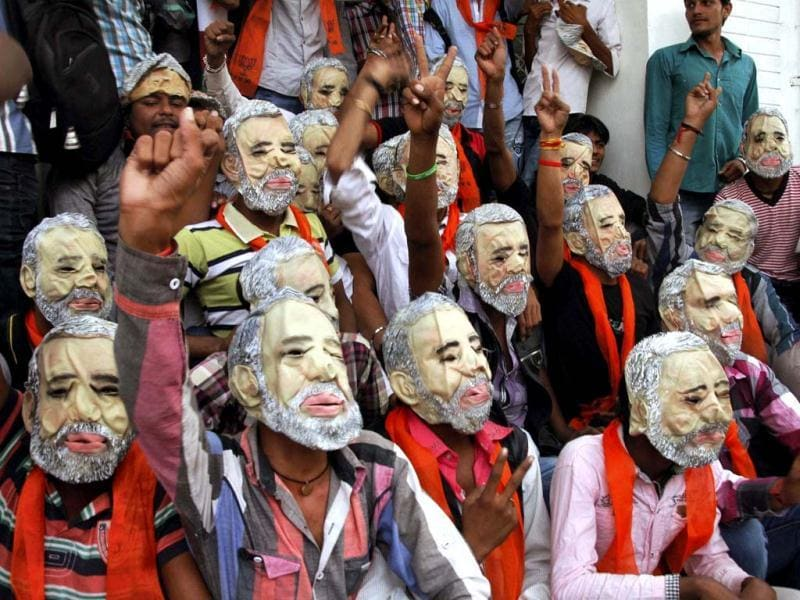 Gujarat chief minister Narendra Modi led the BJP to victory for a record third time in a verdict that strengthened his prospects of being the party's prime ministerial candidate in 2014. BJP workers wear masks of Narendra Modi at an election rally in Ahmedabad on Tuesday. PTI Photo