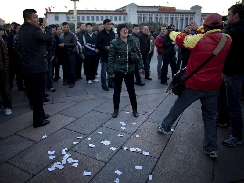 A woman, center, yells after she threw protest papers on Tiananmen Square after a flag raising ceremony while a plainclothes security person, in red, stops a journalist, right, from taking videos, near the Great Hall of the People, where the 18th Communist Party Congress will be held later in the morning, in Beijing, . (AP Photo/Alexander F. Yuan)
