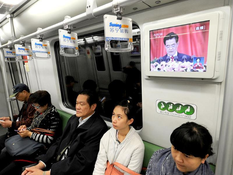 Chinese President Hu Jintao is seen speaking at the opening of the 18th Communist Party Congress on a television in a subway train in Shanghai. AFP Photo/Peter Parks