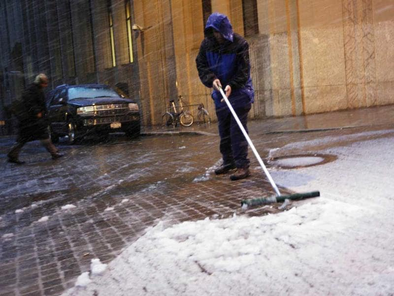 A worker clears snow outside the New York Stock Exchange in New York's financial district. A wintry storm dropped snow on the Northeast and threatened to bring dangerous winds and flooding to a region still climbing out from the devastation of Superstorm Sandy. Reuters/Brendan McDermid