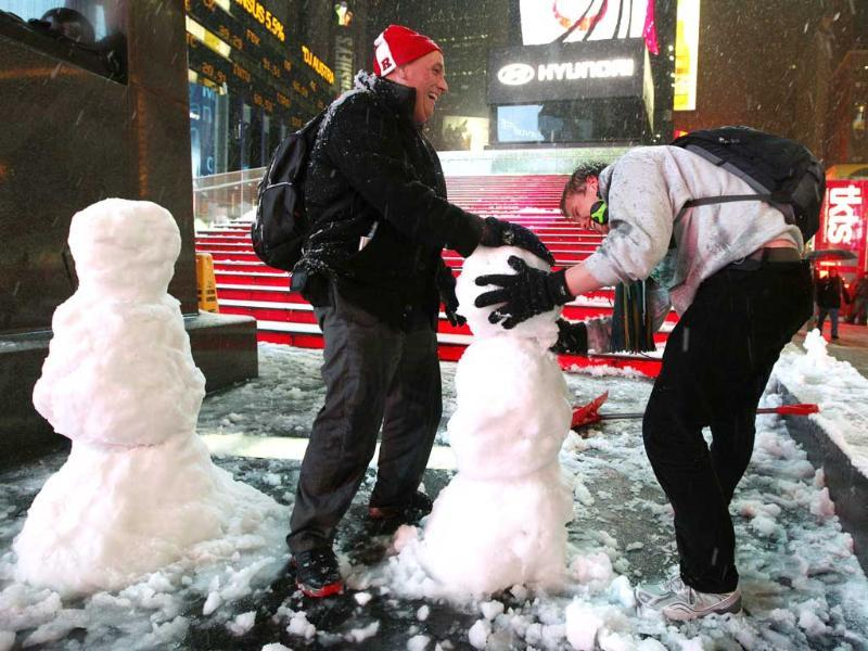 John from Wayne, New Jersey and Henrik, a tourist visiting from Norway, build a snowman together during a snow storm in New York's Times Square. Reuters/Brendan McDermid
