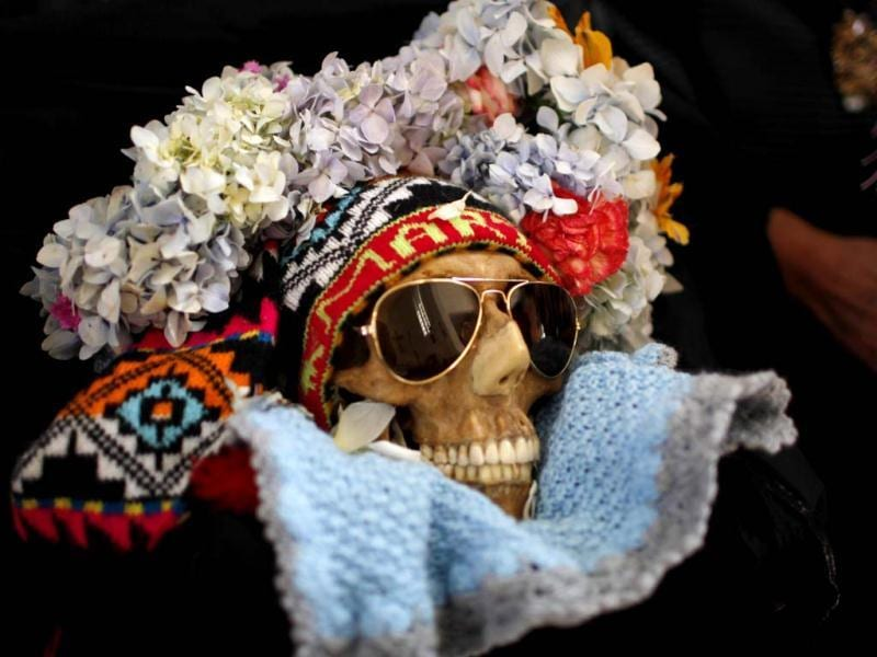 A decorated human skull or Natita is carried out of the Cementerio General's chapel and to the Natitas Festival at the largest cemetery in La Paz, Bolivia. (AP Photo)
