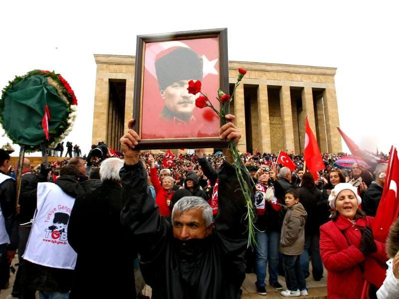 People carry Turkish flags and portraits of Turkey's founder Mustafa Kemal Ataturk as they gather at his mausoleum during a ceremony marking the 74th anniversary of his death in Ankara. AFP/Adem Altan