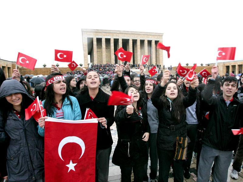 People wave Turkish flags as they gather at the mausoleum of Turkey's founder Mustafa Kemal Ataturk during a ceremony marking the 74th anniversary of his death in Ankara. AFP/Adem Altan