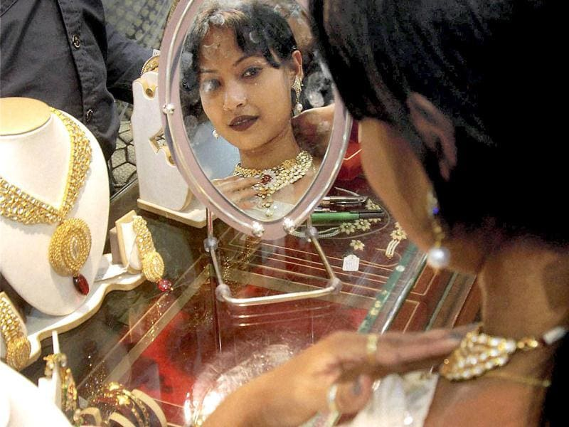 A woman tries out a necklace at a jewellery shop, on the occassion of Dhanteras in Guwahati. PTI