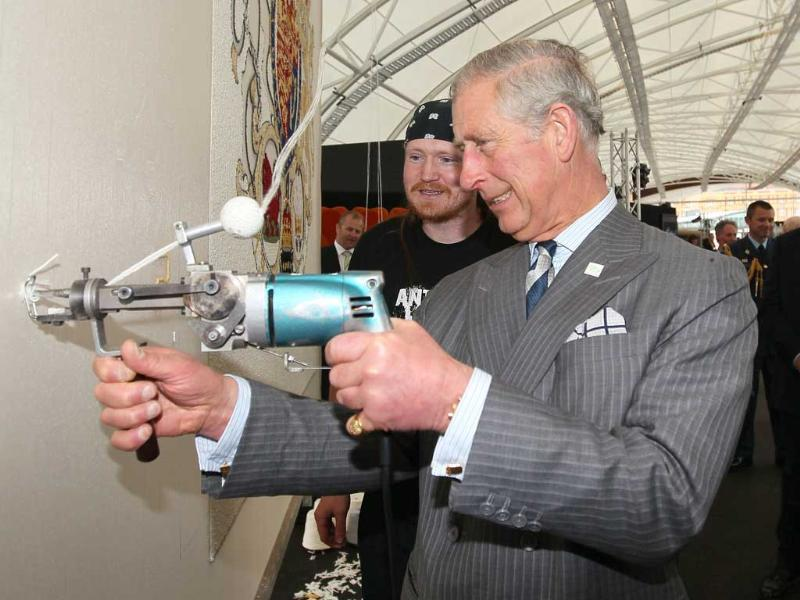 Britain's Prince Charles tries his hands at making a wool rug as demonstrated by Sam Maloney of Dilana Rugs during a Shear Brilliance wool promotion at the Cloud, in Auckland. AFP photo