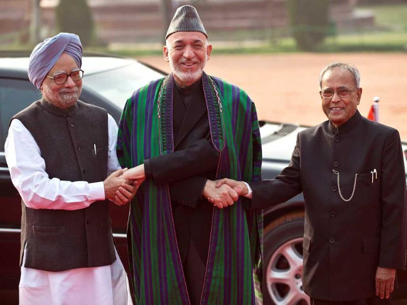 Afghan President Hamid Karzai shakes hands with President Pranab Mukherjee and Prime Minister Manmohan Singh during a ceremonial reception in New Delhi. Karzai is on five day state visit to India till November 13. AFP photo