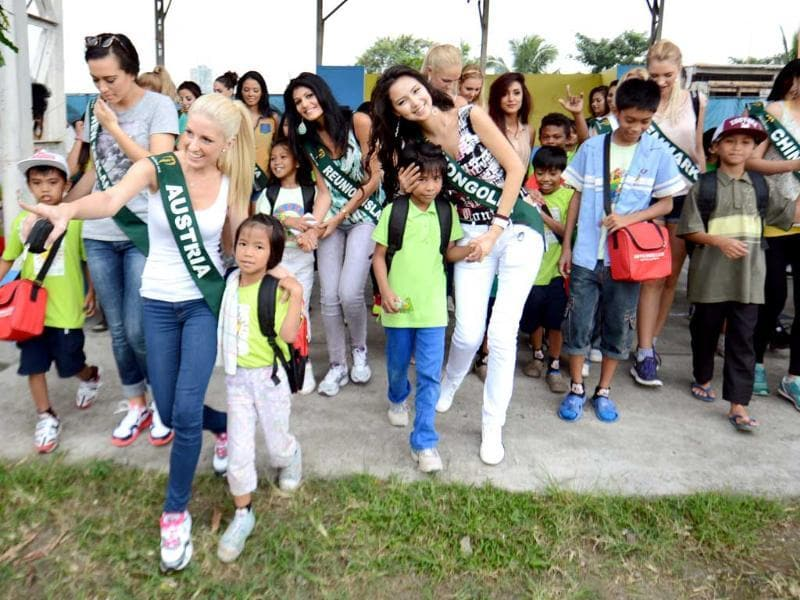 Miss Earth contestants walk with street children to a waiting bus during a visit to a government-run shelter for street children in Manila. Around 91 contestants from around the globe will be vying for this year's crown, which will be held on November 24. AFP photo
