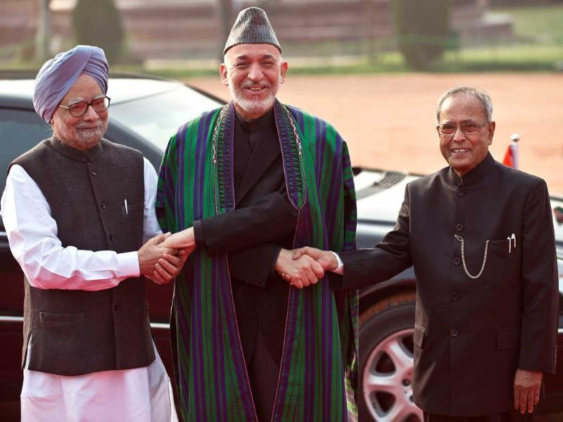 Afghan President Hamid Karzai shakes hands with President Pranab Mukherjee and Prime Minister Manmohan Singh during a ceremonial reception in New Delhi. AFP Photo
