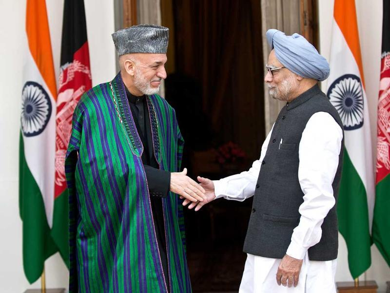 Afghanistan President Hamid Karzai shakes hands with Prime Minister Manmohan Singh prior to delegation level talks and an agreement signing in New Delhi. AFP Photo