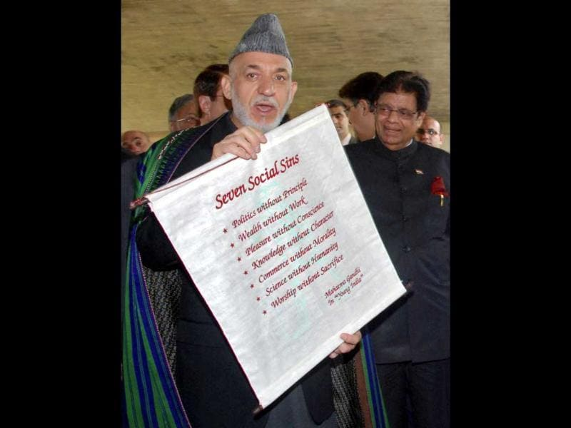 Afghanistan's President Hamid Karzai displays a scroll to the media at the Mahatma Gandhi memorial at Rajghat in New Delhi. Reuters