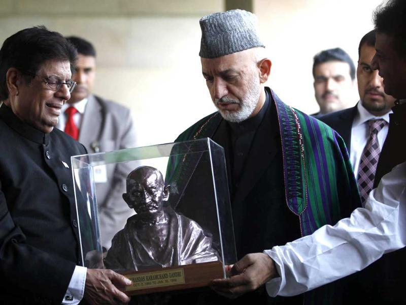 Afghan President Hamid Karzai, center, is presented with a bust of Mahatma Gandhi as he visits the memorial in New Delhi. AP Photo